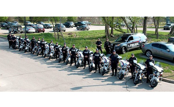 A line of police officers standing beside police motorcycles along with a police SUV