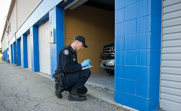A man in TPS uniform kneels writing into a notepad by an open garage door