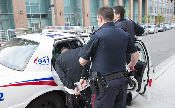 A handcuffed man ducks into the back seat of a TPS car as a man In TPS uniform holds his arm and another gets in a the car