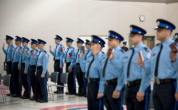 Men and women in blue court officer uniforms and hats stand up with their hands or with bibles in their hands in taking an oath.