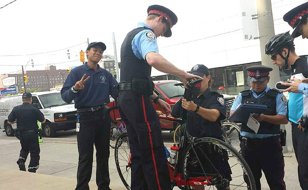 A boy in TPS YIPI uniform flashes a peace sign as a man in TPS Auxiliary uniform holds a bicycle as a woman in TPS uniform inspects it. Another man in TPS Auxiliary uniform writes notes as he speaks to a man in a bicycle helmet.