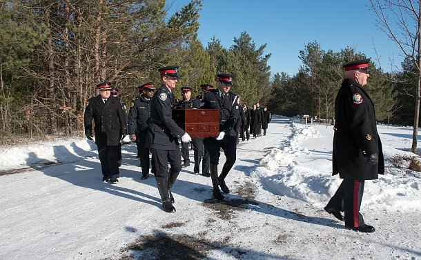 Two men carrying a large wooden box, marching behind them are uniformed officers