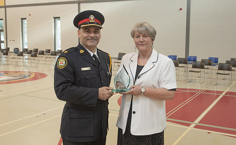 A man in TPS uniform holding an award with a woman