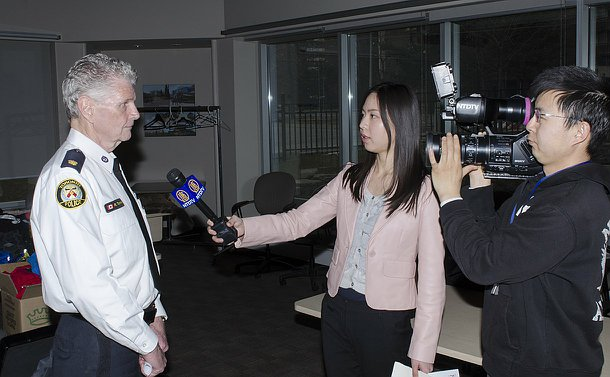 A man in TPS uniform speaks to a woman holding a microphone and a man holding a video camera