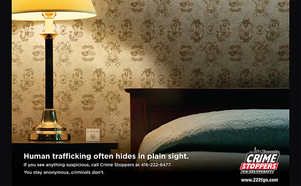 A bed and lamp. Wall paper has huddled girl on the pattern. Text: Human Trafficking often hides in plain sight. If you see anything suspicious, call Crime Stoppers at 416-222-8477. You stay anonymous, criminals don't.
