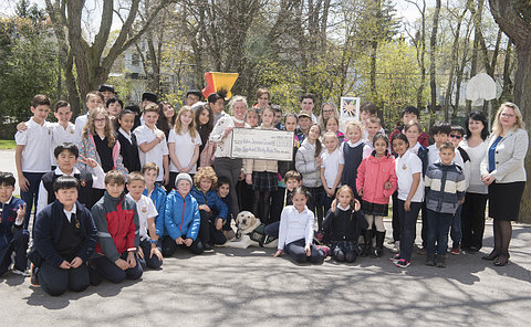 A group of kids, adults, a dog in a schoolyard some hold oversize cheque