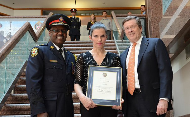 A man in TPS uniform with a woman holding a framed certificate and another man