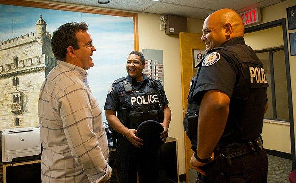 Two men in TPS uniform speak to another man