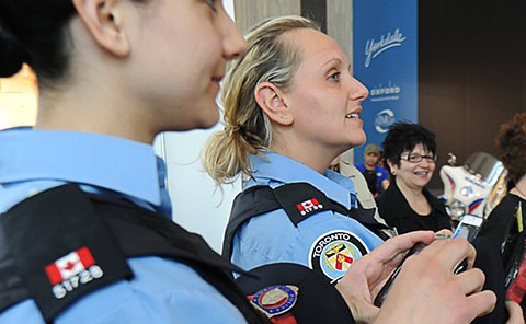 Two women in TPS auxiliary uniforms holding phones