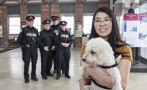 A woman holding a dog in front of four TPS officers