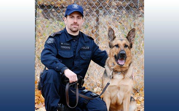 A man in TPS uniform kneeling beside a dog