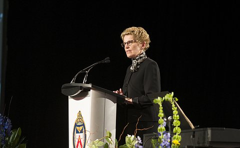 A woman stands at a podium speaking