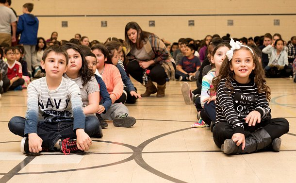 Children sitting in lines at a school gym