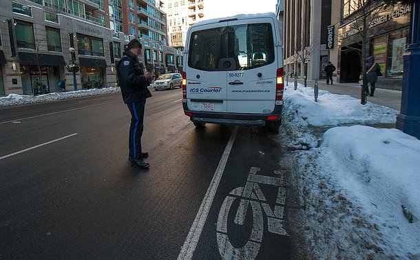 A man in a parking enforcement uniform standing behind a courier van writing a ticket.