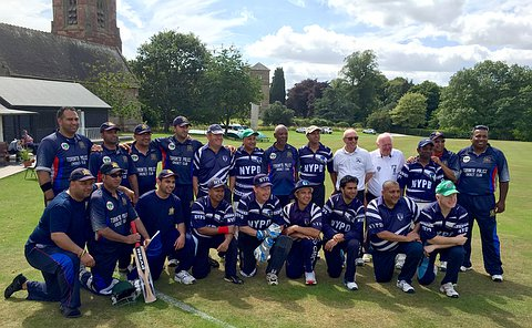 Two cricket teams in blue cricket uniforms posing for a photo on a cricket pitch