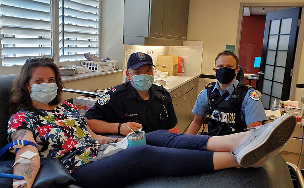 A woman lying in bed, donating blood, with two man in uniforms by her side.