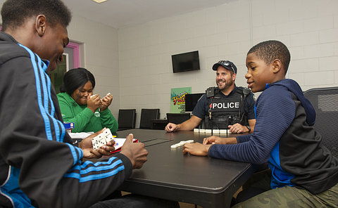 A man in TPS uniform playing dominoes with teens at a table
