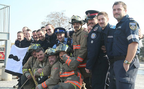 A group of men and women in TPS, Toronto Fire and Toronto Paramedic uniforms hold a banner with a moustache