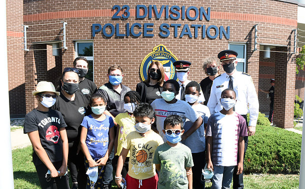 Group of adults and children, all wearing face masks, standing in front of a building with a sign 23 Division on it