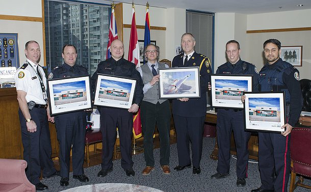 Six men in Toronto Police uniform hold framed prints of an airplane with another man standing in a line