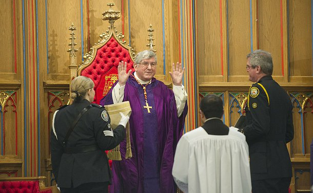A man in Cathlolic clergy regalia with a man and woman in TPS uniform