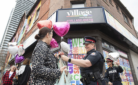 A woman in police uniform talking to another woman holding balloons