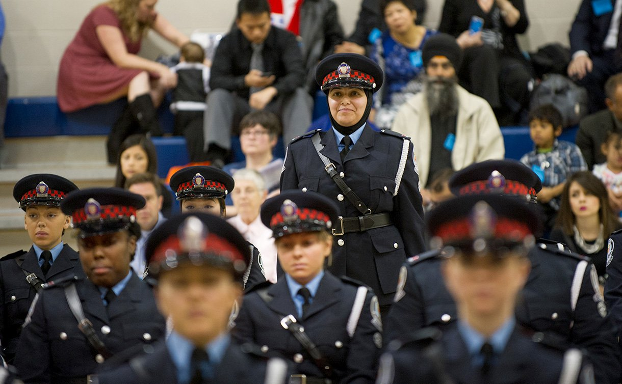A woman in auxiliary uniform standing while everyone around her is sitting.