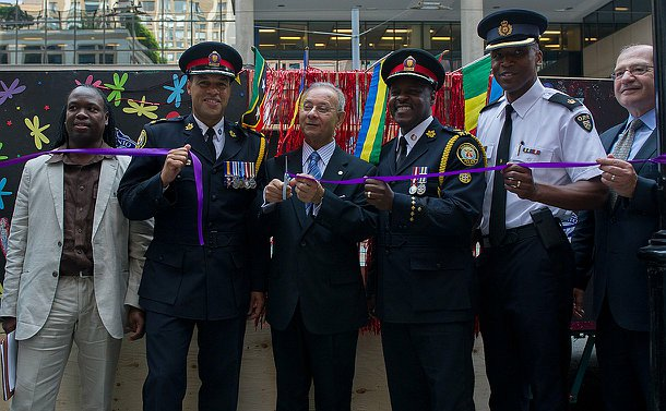 Three men in uniform and two in civilian clothes stand in front of a purple ribbon which has just been cut.