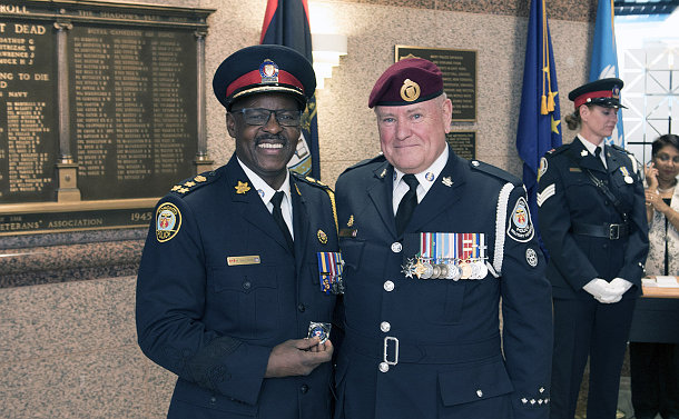 Two men in police uniforms, one is holding a medal in his hand