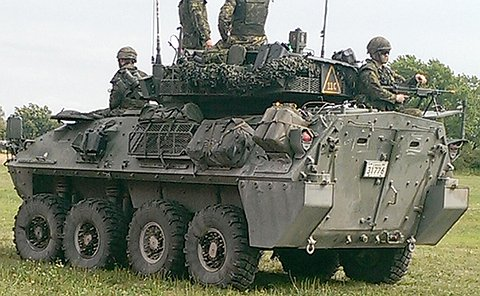 People in army fatigues atop a eight-wheeled armoured military vehicle