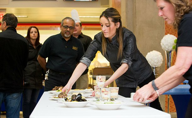 A woman in a chefs uniform putting meals on plates down on a table