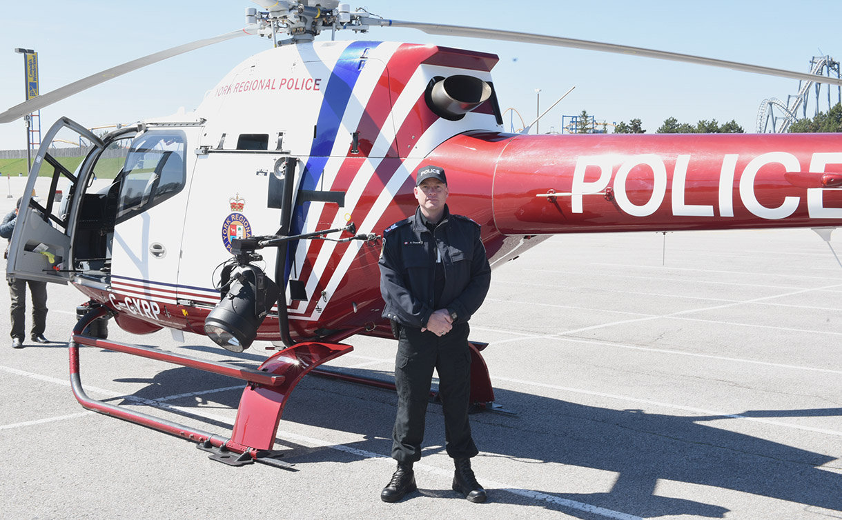 Man in a uniform standing in-front of a police helicopter