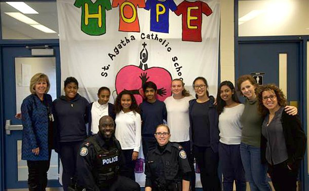 A male and female in TPS uniform kneel in front of a group of women and girls in front of a banner with the word hope