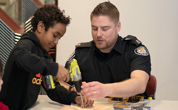 A man in TPS uniform helping a child use a drill