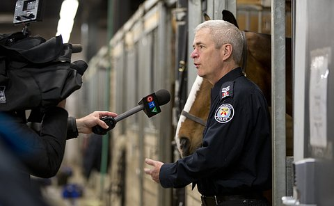 A man in TPS uniform holding a horse's reins while talking to a microphone and video camera