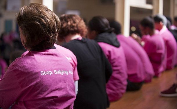 The backs of people sitting in a line wearing pink T-shirts