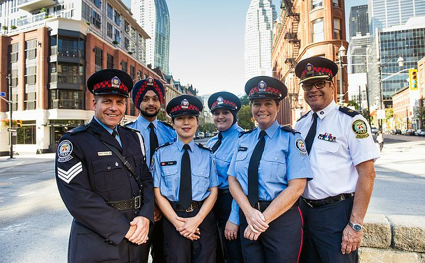Six Auxiliary officers standing in front of toronto's flat iron building in uniform