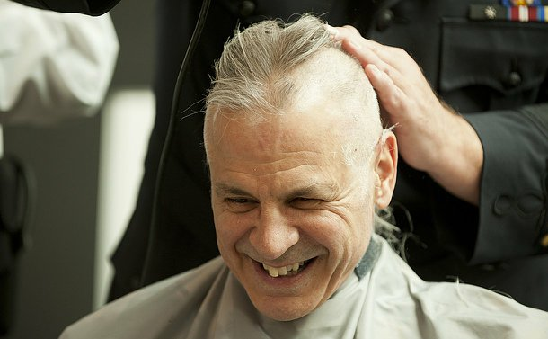A man with half his head shaved smiles