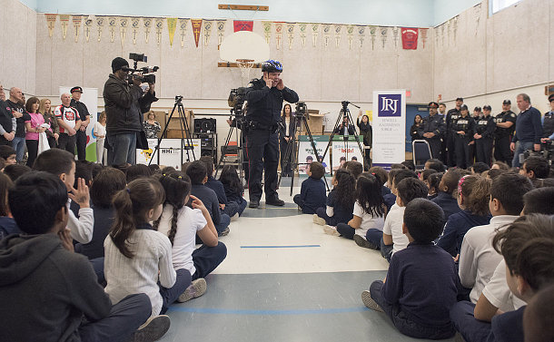 A man in TPS uniform wearing a bike helmet in a gym talking to seated children