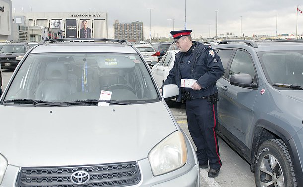 A man in TPS uniform holds the door handle of a car in a parking lot holding leaflets in one hand