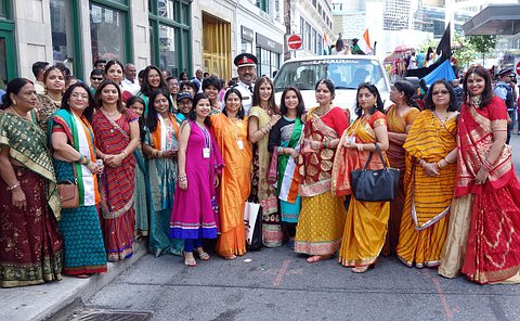 Women dressed in traditional Indian saris' and suits with a man in the middle wearing a police uniform