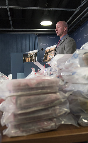 A man at a podium behind plastic bags with bundled packages