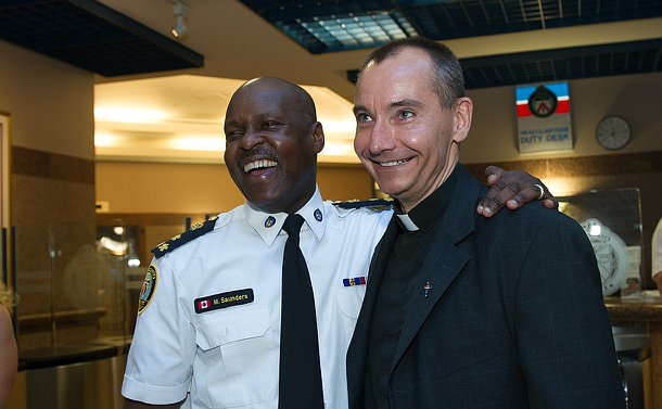A man in TPS uniform embraces a man in a clerical collar