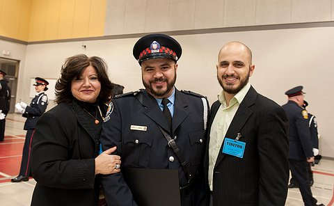 An officer with his mother and brother on his sides.