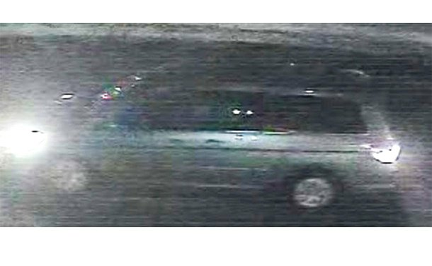A pixelated surveillance image of a mini van