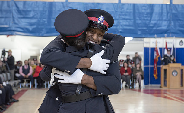 A man and woman in TPS uniform hug