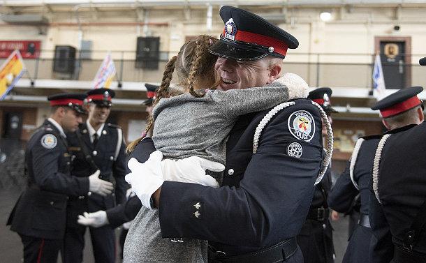 A man in TPS uniform hugging a girl