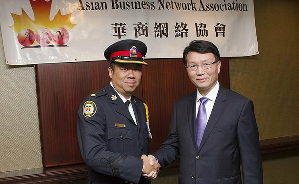 One man in TPS uniform shakes the hand of another man