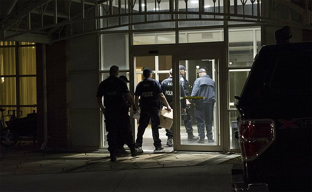 A group of men in TPS uniform enter a building in darkness