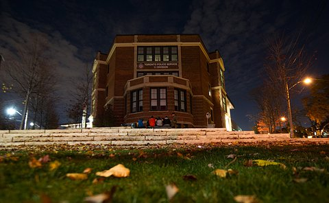 a wide angle shot of 11 Division police station from a low lying angle. It is at night and the streetlights are one.